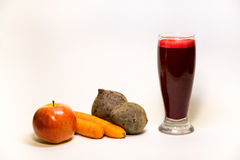 Beet root carrot apple fresh raw juice. Beet root carrot apple and a glass of fresh raw juice isolated on white background Royalty Free Stock Images