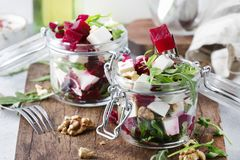 Beet salad with arugula, goat cheese and nuts, trendy salad jar, gray kitchen table background, selective focus. Beet salad with arugula, goat cheese and nuts royalty free stock photos