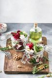 Beet salad with arugula, goat cheese and nuts, trendy salad jar, gray kitchen table background, selective focus. Beet salad with arugula, goat cheese and nuts royalty free stock image