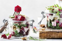 Beet salad with arugula, goat cheese and nuts, trendy salad jar, gray kitchen table background, selective focus. Beet salad with arugula, goat cheese and nuts stock photos