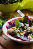 Beet salad with feta cheese and walnuts. Salad: beet salad with feta cheese and walnuts on wooden background Stock Photos