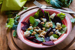 Beet salad with feta cheese and walnuts. Salad: beet salad with feta cheese and walnuts on wooden background Stock Photo