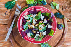 Beet salad with feta cheese and walnuts. Salad: beet salad with feta cheese and walnuts on wooden background. Top view Royalty Free Stock Photos