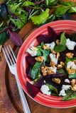 Beet salad with feta cheese and walnuts. Salad: beet salad with feta cheese and walnuts on wooden background. Top view Royalty Free Stock Photography