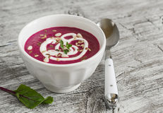 Beet soup in a white bowl on bright wooden surface Royalty Free Stock Photos