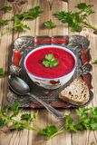 Beet soup. On a wooden table top decorated with parsley stock photo