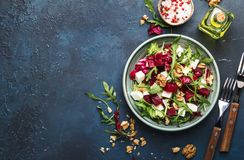 Beet summer salad with arugula, radicchio, soft cheese and walnuts on plate with fork, dressing and spices on blue kitchen table, royalty free stock images