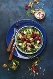 Beet summer salad with arugula, radicchio, soft cheese and walnuts on plate with fork, dressing and spices on blue kitchen table,. Copy space, top view stock photo