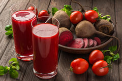 Beet-tomato juice with vegetables on dark wooden background royalty free stock photo