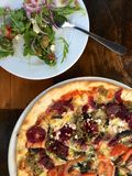 Beet, tomato and pesto pizza and arugula salad with olives stock photos