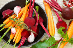 Beetroot and carrots. Fresh raw vegetables on the baking tray ready for roasting with thyme and spices Stock Images