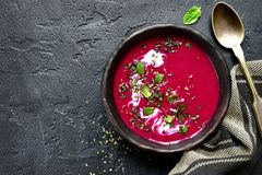 Beetroot creamy soup.Top view with copy space. Beetroot creamy soup in a dark clay bowl over black slate,stone or concrete background.Top view with copy space royalty free stock photography