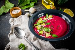Beetroot gazpacho soup. Vegan food, summer cold Beetroot gazpacho soup with lemon, avocado and fresh herbs copy space top view royalty free stock photo