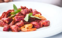 Beetroot gnocchi and prawns garnished with mint royalty free stock photos