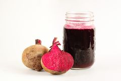 Beetroot juice on white background. Beetroot juice in a mason jar mug with one of the beetroot sliced half on white isolated color background stock photo