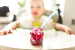 Beetroot puree for babies. In a jar, the child is in the background out of focus royalty free stock photo