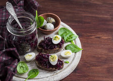 Beetroot relish and a sandwich with beets, quail egg and spinach on rustic light wooden board. Stock Photo