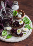 Beetroot relish and a sandwich with beets, quail egg and spinach on rustic light wooden board. Stock Image