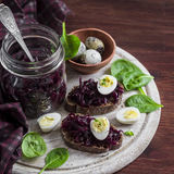 Beetroot relish and a sandwich with beets, quail egg and spinach on rustic light wooden board. Royalty Free Stock Photo