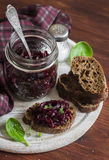 Beetroot relish and slices of rye bread on rustic wooden board. Healthy breakfast or snack. Stock Photos