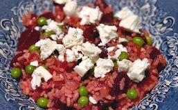 Beetroot risotto with cream goats cheese. Beet with rice and feta in blue bowl Royalty Free Stock Photography