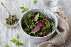 Beetroot salad with baked red onion, capers, watercress, greens and vinaigrette sauce. Vegan healthy food. In a blue bowl on a wooden table Royalty Free Stock Images