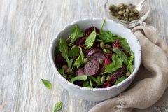 Beetroot salad with baked red onion, capers, watercress, greens and vinaigrette sauce. Vegan healthy food. In a blue bowl on a wooden table with free space Royalty Free Stock Images