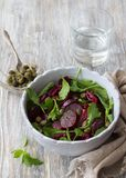 Beetroot salad with baked red onion, capers, watercress, greens and vinaigrette sauce. Vegan healthy food. In a blue bowl on a wooden table Royalty Free Stock Image