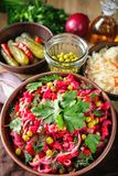 Beetroot salad vinaigrette in a clay bowl. Vinaigrette salad with boiled vegetables, pickled cucumbers, sauerkraut and canned green peas in a clay bowl royalty free stock photos