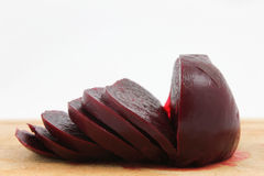 Beetroot sliced. Cooked beetroot sliced on chopping board against a white background Stock Image