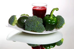 Beetroot smoothie in glass, near fresh broccoli, green pepper, avocado Stock Photo
