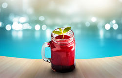 Beetroot smoothie healthy and mint herb on wooden and blue swiming pool background. Beetroot smoothie healthy and mint herb on wooden and blue swiming pool Stock Image