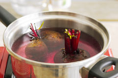 Beetroot soup. Saucepan showing three beetroot with shoots in water ready for boiling Stock Photos