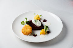 Beetroot terrine, goat cheese croquettes, horseradish sauce and dill cream on white dish.  royalty free stock photo