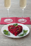 Beetroot and vegetables salad made in heart shape served with herbs on plate with two glasses of champagne Stock Image