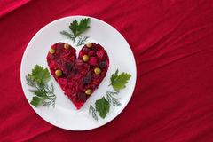 Beetroot and vegetables salad made in hearth shape served with herbs on plate Stock Photos