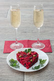 Beetroot and vegetables salad made in hearth shape served with herbs on plate with two glasses of champagne Stock Photos