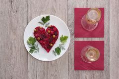 Beetroot and vegetables salad made in hearth shape served with herbs on plate with two glasses of champagne against wooden backgro Royalty Free Stock Photo