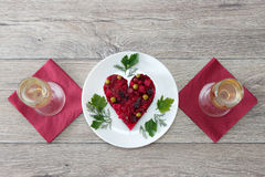 Beetroot and vegetables salad made in hearth shape served with herbs on plate with two glasses of champagne against wooden backgro Royalty Free Stock Photos