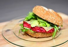 Beetroot burger with arugula. Closeup of beetroot burger with grilled arugula on wooden plate stock photography