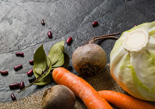 Beets, carrots and cabbage during cooking. Composition on a dark background. Royalty Free Stock Image