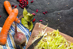 Beets, carrots and cabbage during cooking. Composition on a dark background. Royalty Free Stock Photos