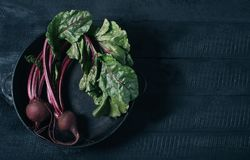 Beets with green tops in round metal pan on dark black wooden background, fresh red beetroot on backdrop kitchen table top view, stock photos