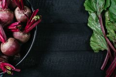 Beets with green tops in round metal pan on dark black wooden background, fresh red beetroot on backdrop kitchen table top view stock photo