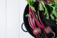 Beets with green tops in round metal pan on white wooden background, fresh red beetroot on backdrop kitchen table top view royalty free stock photo