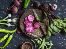 Beets, peppers, onions, green beans, spices on a dark background. Fresh garden vegetables. Stock Photos