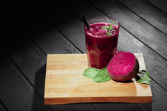 Beets and salads on a wooden background. Glass of beetroot drink on a cutting desk. Vegetarian cafe concept. Copy space. A glass of thick beetroot juice and stock photo