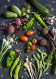 Beets, zucchini, peppers, onion, garlic, green beans, beans, tomatoes, parsnips, cucumbers - fresh vegetables on a dark backgroun Stock Photos