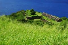 Befästningar och byggnader för svavelkullefästning med grönt gräs och det ljusa blåa havet Royaltyfri Fotografi