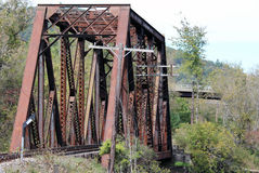 Befördern Sie Brücke mit neuer Straßen-Brücke hinter ihr mit dem Zug stockfotos